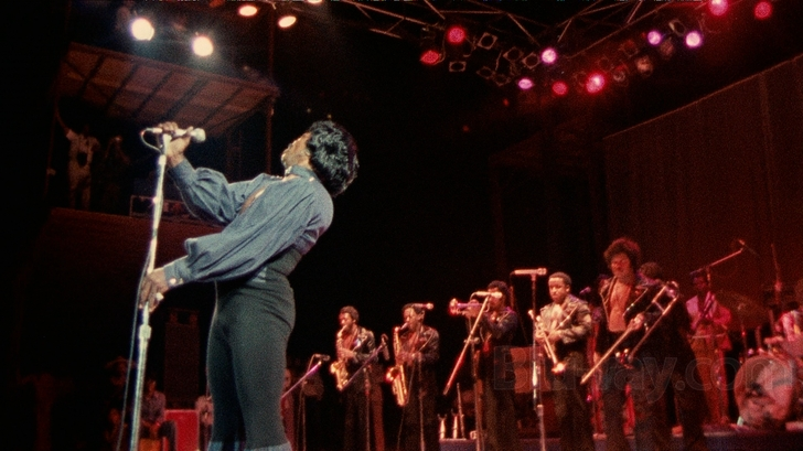 James Brown holds a microphone in front of a brass section on a stage.